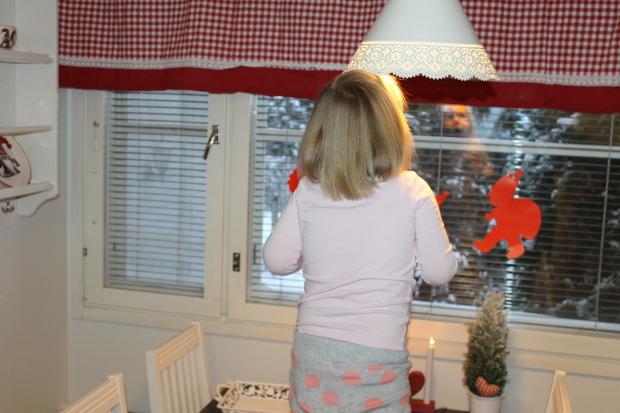 Innokas joulupukin odottaja nousi pöydällle kurkistamaan ikkunasta
