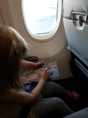 Amalia tekee puuhakirjaa lentokoneessa